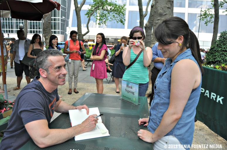 DAN SAVAGE (LEFT) SIGNS HIS BOOK FOR A FAN AT BRYANT PARK'S READING ROOM, NY